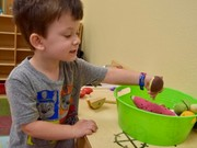 A Shawnee Early Childhood student plays with toys in a learning center.